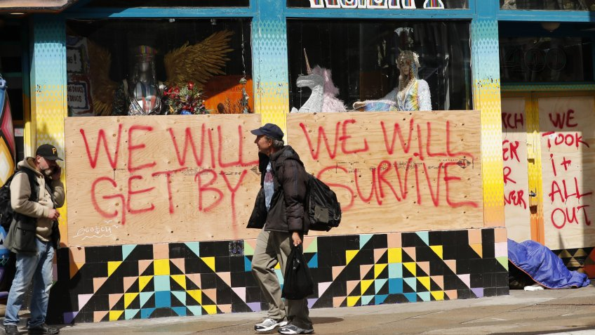 A boarded window at a closed store with a message in the Haight-Ashbury district, 'We Will Get By, We Will Survive' in San Francisco, California, USA, 18 March 2020.