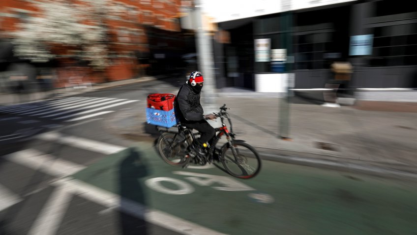 A food delivery person rides down Ninth Avenue in New York, New York, USA, 22 March 2020.