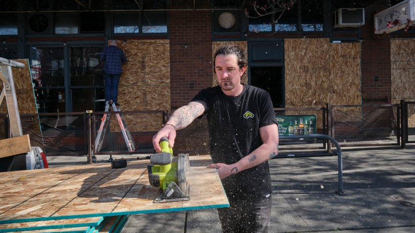 Friend and fellow restaurant owner Brian Patrick saws a piece of plywood while help to board up the windows a pizza restaurant owned by Brian Lee in Seattle, Washington, USA, on 20 March 2020.