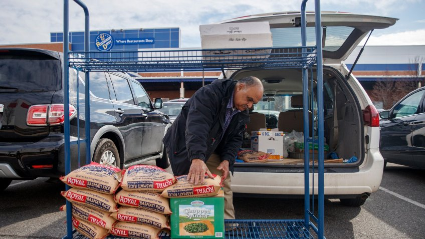 A shopper loads his vehicle at Restaurant Depot, a restaurant supply warehouse, amid the COVID-19 coronavirus pandemic in Alexandria, Virginia, USA, 21 March 2020.